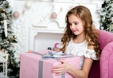 Portrait of adorable happy smiling little girl child in princess dress sitting in the chair with gift box near fir tree. In christmas time royalty free stock photos