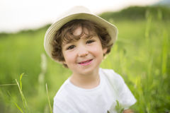 Portrait of adorable kid boy with hat standing on a summer meadow Royalty Free Stock Image