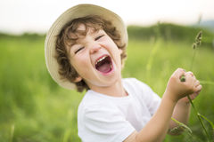 Portrait of adorable kid boy with hat standing on a summer meadow Royalty Free Stock Images