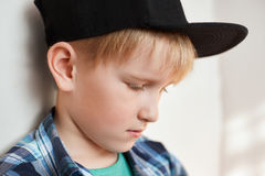 Portrait of adorable little boy with blond hair wearing stylish clothes and cap having thoughtful expression looking down standing. Near white wall. Beautiful Stock Image