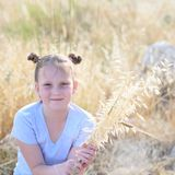 Portrait adorable little girl, age 9-10 on yellow autumn field. royalty free stock image