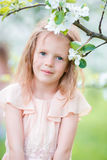 Portrait of adorable little girl in blooming apple tree garden on spring day Royalty Free Stock Images