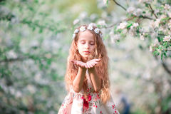 Portrait of adorable little girl in blooming cherry tree garden outdoors Stock Images