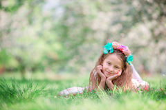 Portrait of adorable little girl in blooming cherry tree garden outdoors Stock Photos