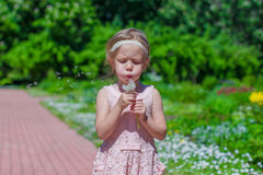 Portrait of adorable little girl blowing a Royalty Free Stock Images