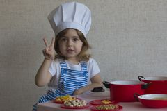 Portrait Adorable little girl in chef hat cook food. shows fingers a victory. Portrait cute smiling chef cook girl enters the frame and standing at the kitchen royalty free stock photo