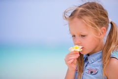 Portrait of adorable little girl with flower on beach summer vacation Stock Images