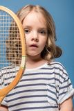 Portrait of adorable little girl holding tennis raquet and looking at camera. On blue stock photo