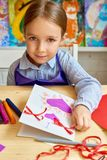 Cute Girl Making Handmade Card for Mom. Portrait of adorable little girl looking at camera while making gift card for mom during art and craft class in pre Royalty Free Stock Photos