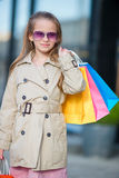 Portrait of adorable little girl with shopping bags outdoors. Fashion toddler kid in european city outdoors Royalty Free Stock Photo