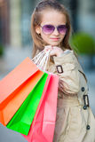 Portrait of adorable little girl with shopping bags outdoors. Fashion toddler kid in european city outdoors Royalty Free Stock Image