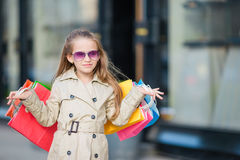 Portrait of adorable little girl with shopping bags outdoors. Fashion toddler kid in european city outdoors Royalty Free Stock Photography