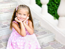 Portrait of adorable little girl sitting on steps Royalty Free Stock Image