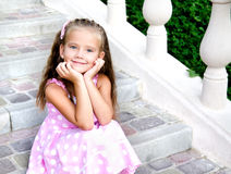Portrait of adorable little girl sitting on steps Royalty Free Stock Photography