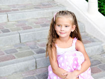 Portrait of adorable little girl sitting on steps Stock Photo