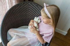 Portrait of adorable little girl with stuffed teddy bear in hands posing for photography while sitting on chair stock photo