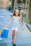 Portrait of adorable little girl walking with shopping bags outdoors in european city. Fashion toddler kid in Italian Royalty Free Stock Photo