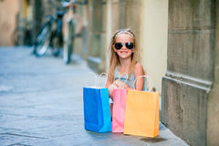 Portrait of adorable little girl walking with shopping bags outdoors in european city. Fashion toddler kid in Italian Stock Images