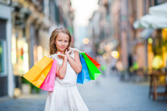 Portrait of adorable little girl walking with shopping bags outdoors in Rome. Fashion toddler kid in Italian city with Stock Photos