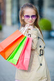 Portrait of adorable little girl walking with shopping bags outdoors Stock Images