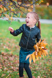 Portrait of adorable little girl with yellow leaves bouquet in fall Stock Images