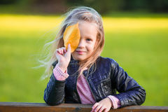 Portrait of adorable little girl with yellow leaves outdoors at beautiful autumn day Royalty Free Stock Photo