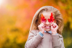 Portrait of adorable little girl with yellow and orange leaves outdoors at beautiful autumn day Stock Photo