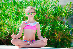 Portrait of adorable little girl in yoga outdoor on vacation. Adorable little sister at beach during summer vacation Stock Images