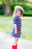 Portrait of adorable little kid girl in summer park. On warm sunny day. Outdoors. Child in red rubber rainboots Royalty Free Stock Photos