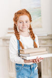 Portrait of adorable little redhead girl holding pile of books Stock Photos