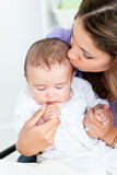 Portrait of an adorable mother kissing her baby Royalty Free Stock Photo