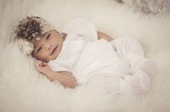 Portrait of adorable newborn baby with floral head band sleeping. In basket covered with furry mat.New life and parenting concept.shot from top angle stock images
