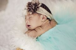 Portrait of adorable newborn baby with floral head band sleeping. In basket covered with furry mat.New life and parenting concept.shot from top angle stock photo