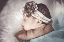 Portrait of adorable newborn baby with floral head band sleeping. In basket covered with furry mat.New life and parenting concept.shot from top angle royalty free stock photography