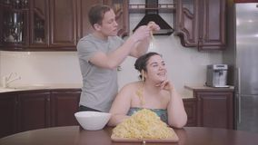 Portrait adorable plump woman sitting in the kitchen at home. The slim blond man hanging noodles on the ears of his fat. The pretty plump woman sitting in the stock video