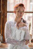 Portrait of a adorable redhead woman. Posing against the window, wearing a white dress stock images
