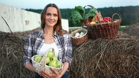 Portrait of rustic woman posing with fresh seasonal harvest near haystack. Medium shot on RED camera