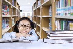 Adorable schoolgirl sitting with textbooks. Portrait of adorable schoolgirl looking at the camera while sitting with textbooks in the library Royalty Free Stock Photography