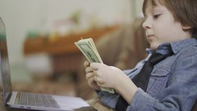 Portrait adorable small boy in jeans jacket sitting on sofa in front of laptop counting the money. A bundle of dollars stock video footage