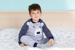 Portrait of adorable small kid in pyjamas, sits crossed legs at comfortable bed in cozy bedroom with blue wall, looks directly int. O camera, going to sleep Royalty Free Stock Photos