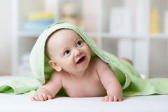 Portrait of adorable smiling baby in hooded towel lying on bed after having bathtime. Portrait of adorable smiling baby boy in hooded towel lying on bed after Stock Images