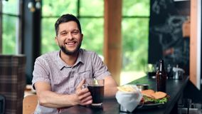 Portrait adorable smiling bearded man posing in sport pub looking at camera feeling positive emotion stock footage