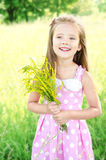 Portrait of adorable smiling little girl with flowers. Outdoor Stock Image