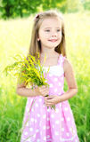 Portrait of adorable smiling little girl with flowers. Outdoor Stock Photo