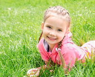 Portrait of adorable smiling little girl lying on grass Royalty Free Stock Image