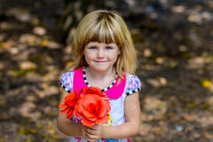 Portrait of adorable smiling little girl with red flowers in her hands. In the park Stock Photos