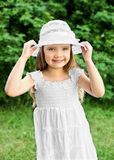 Portrait of adorable smiling little girl in white dress and hat Royalty Free Stock Photography