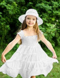 Portrait of adorable smiling little girl in white dress and hat Stock Photos