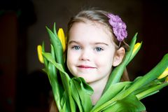 Portrait of adorable sunny child girl with tulips Royalty Free Stock Photo