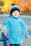 Portrait of adorable toddler boy with blue jacket and colorful u Royalty Free Stock Image